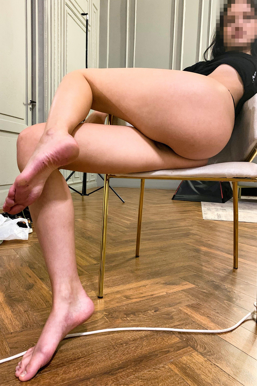 Попа девушки на стуле. Стопы, стройные ноги.